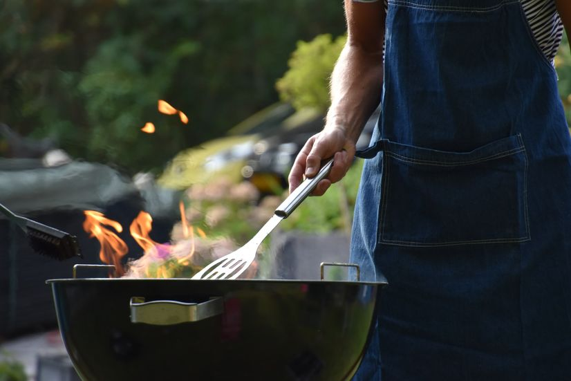 A man in a blue apron using a barbecue.