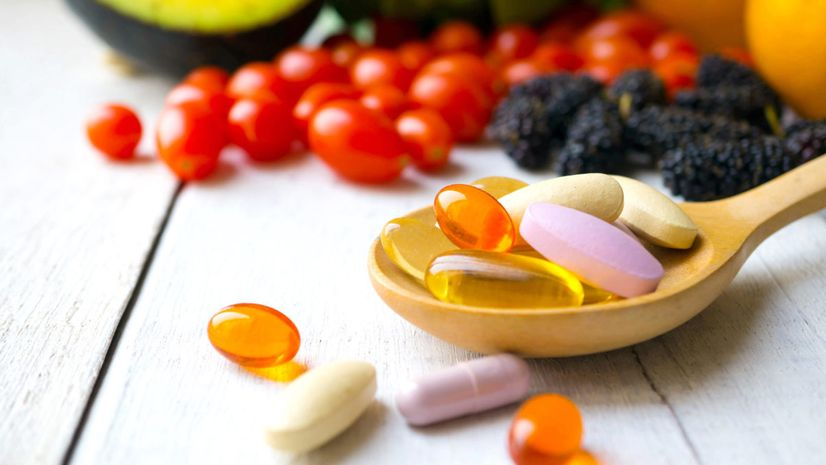 A wooden spoon filled with colourful vitamins in the foreground and an assortment of fresh fruits and vegetables in the background