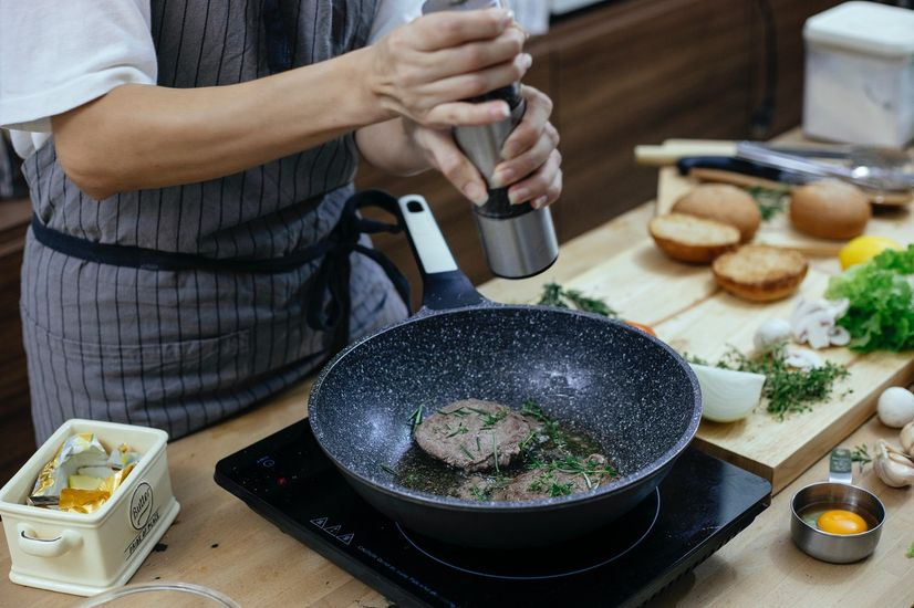 Woman using a portable induction stove to cook meat
