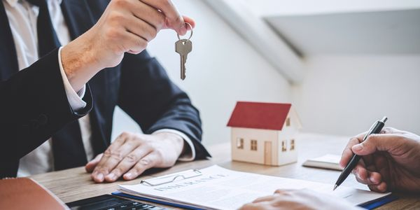 A man at a desk handing over a house key to someone filling out paperwork. There's also a model of a house on the desk.