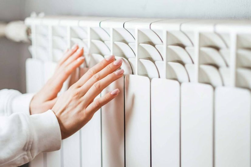 A woman's hand's held up to a white panel heater.