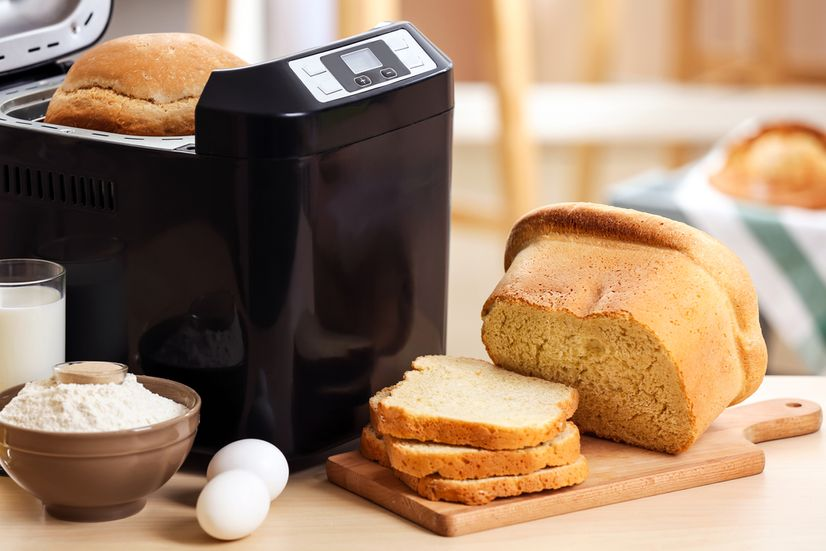 A black bread maker next to a loaf of white bread, two eggs, and a bowl of flour on a kitchen benchtop