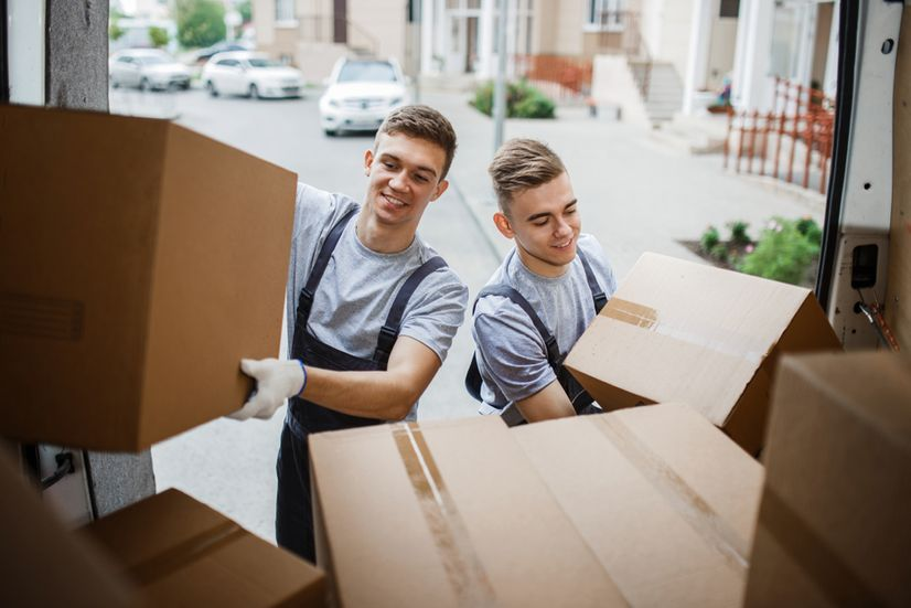 Two furniture removalists removing cardboard boxes from the back of a van