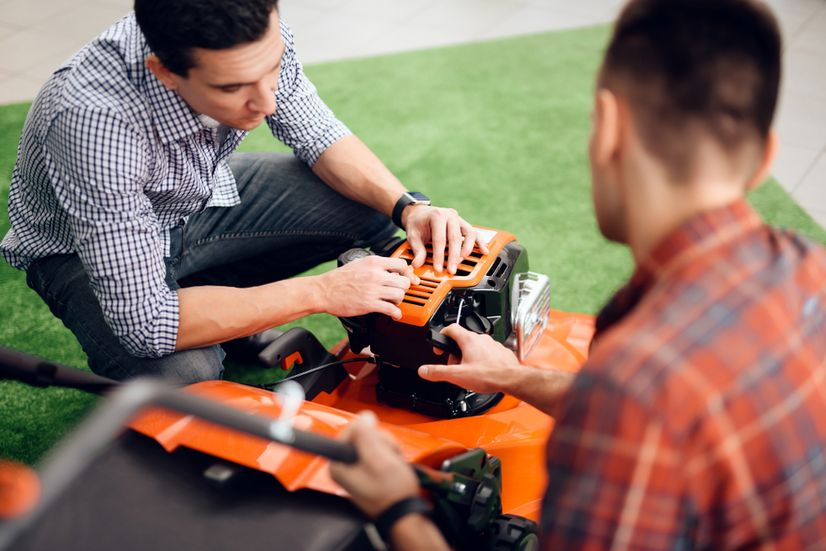 A power tool salesman showing a customer the features of a lawn mower.
