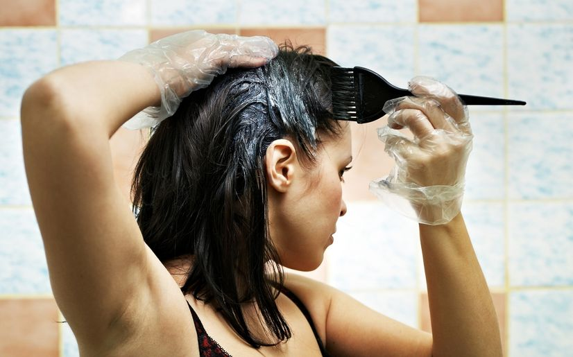 A woman dyeing her hair at home.