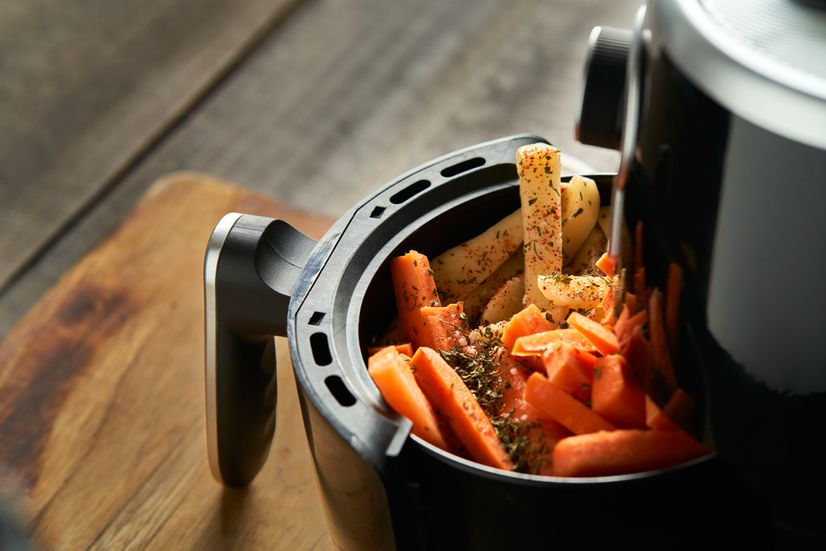 An air fryer with potato and sweet potato chips covered in seasoning in the basket.