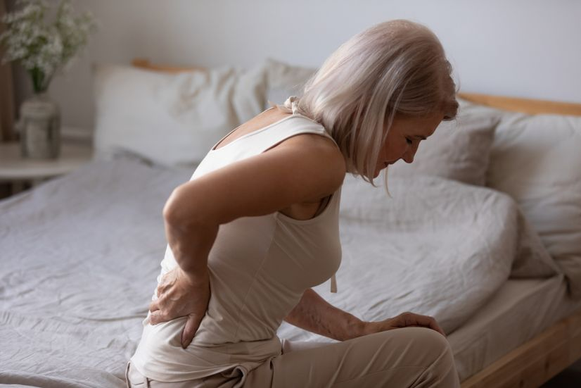 Mature age woman sitting on bed holding her back in pain