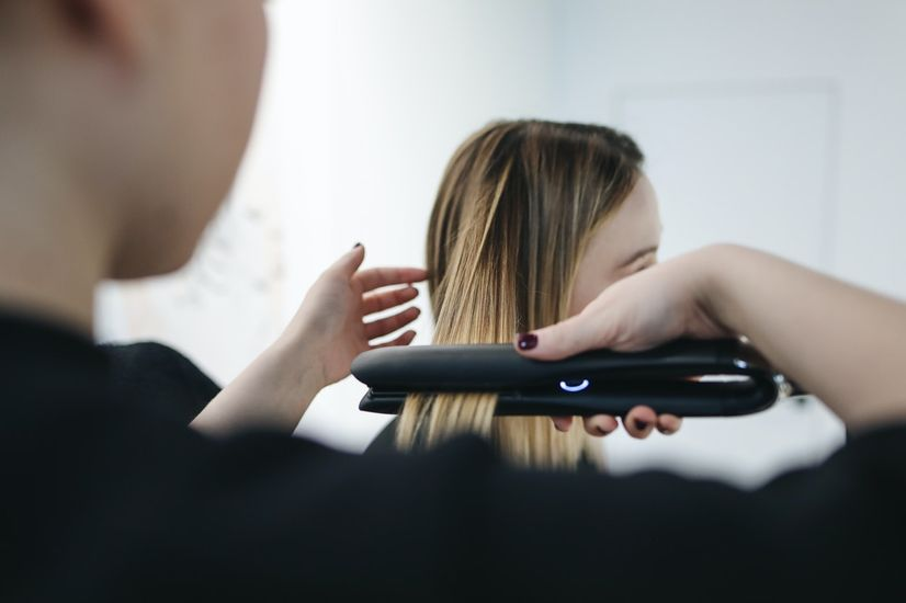 A hair stylist using a hair straightener to straighten the hair of a woman