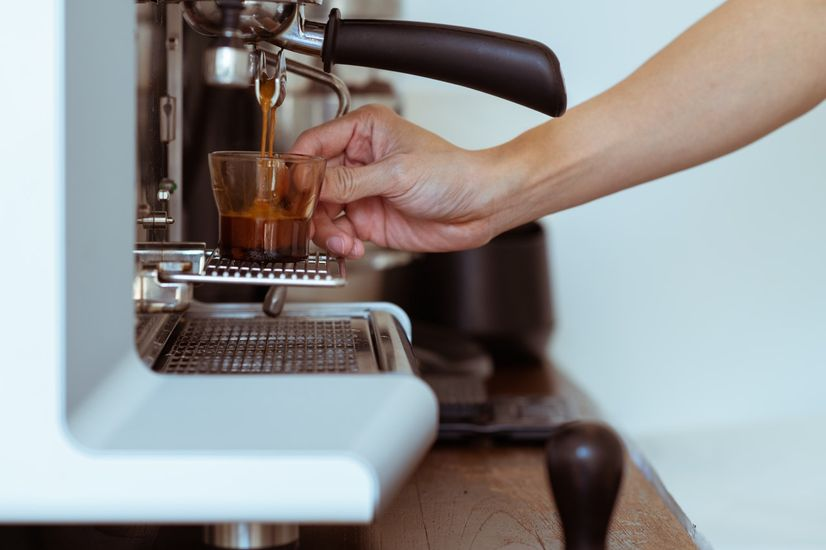 A coffee machine pouring an espresso shot as someone holds the cup.