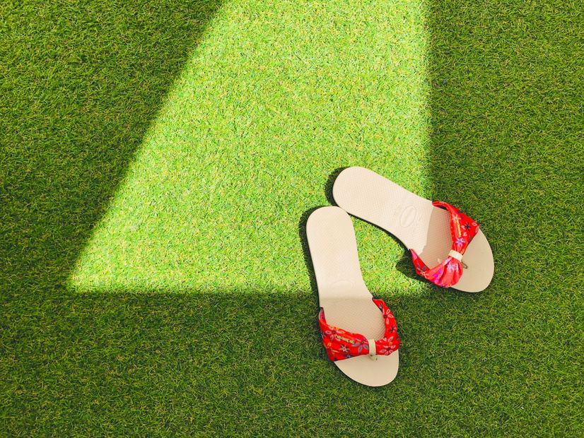 A pair of sandals sitting on an artificial lawn.