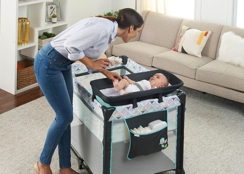Woman cooing at a baby in a portacot with a bassinet insert.