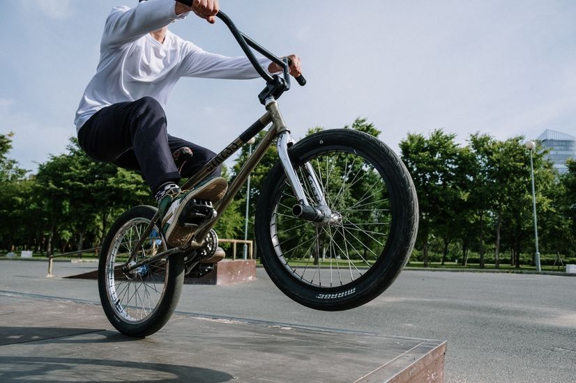 Man in white long sleeved shirt doing a wheelie on a BMX bike at a skate park