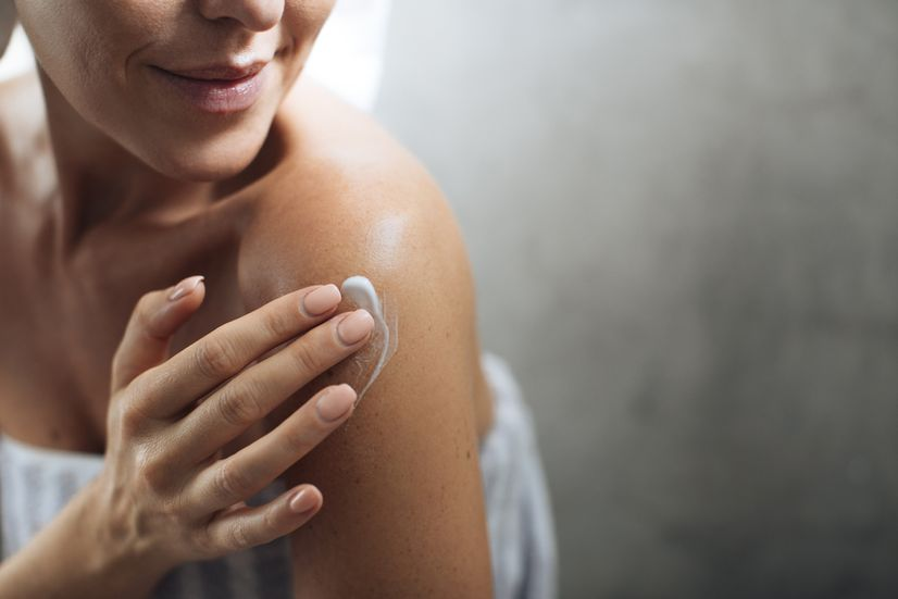 Tanned woman applying lotion on her shoulder in the bathroom