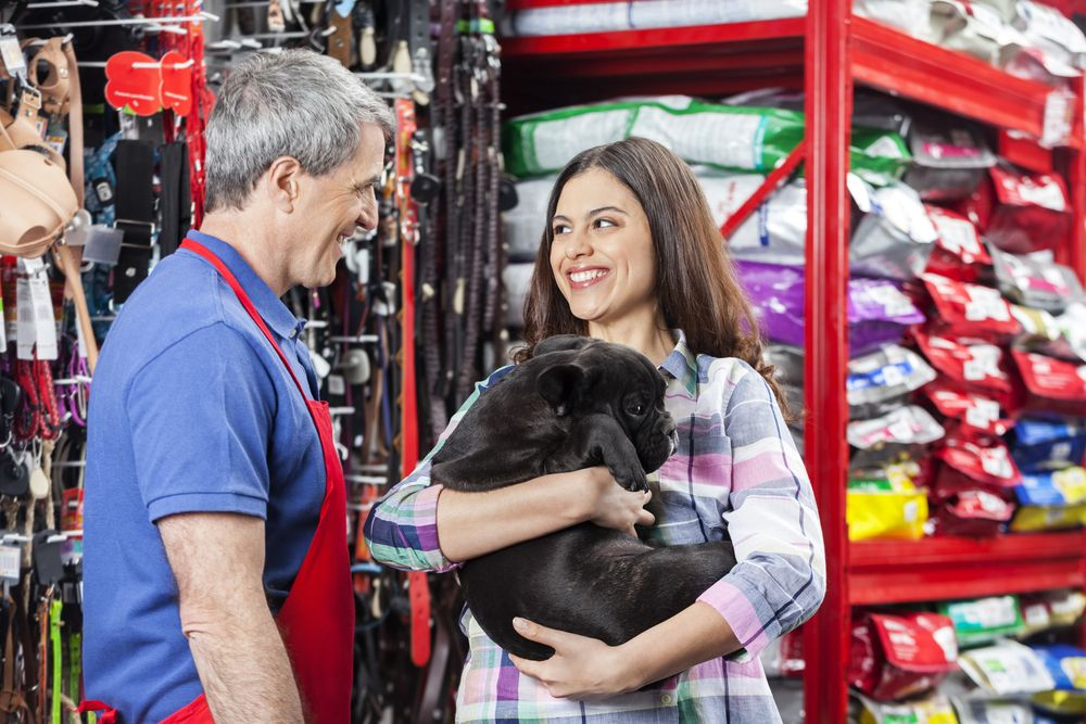 Salesman and woman holding dog in pet store