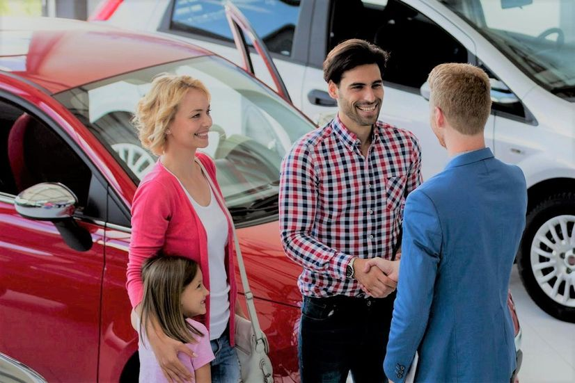 Family shaking on a new deal just made at a car dealership