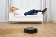 Man relaxing while robovac cleans