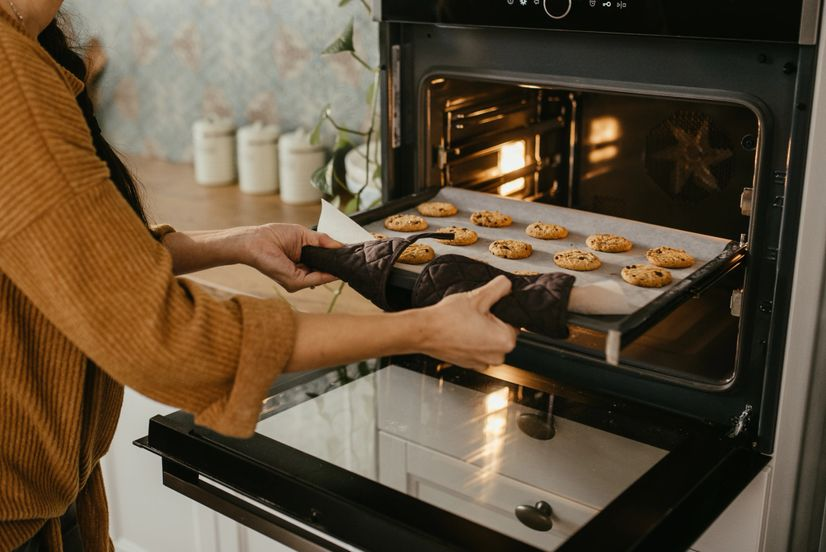 A woman pulling freshly baked cookies out of the oven