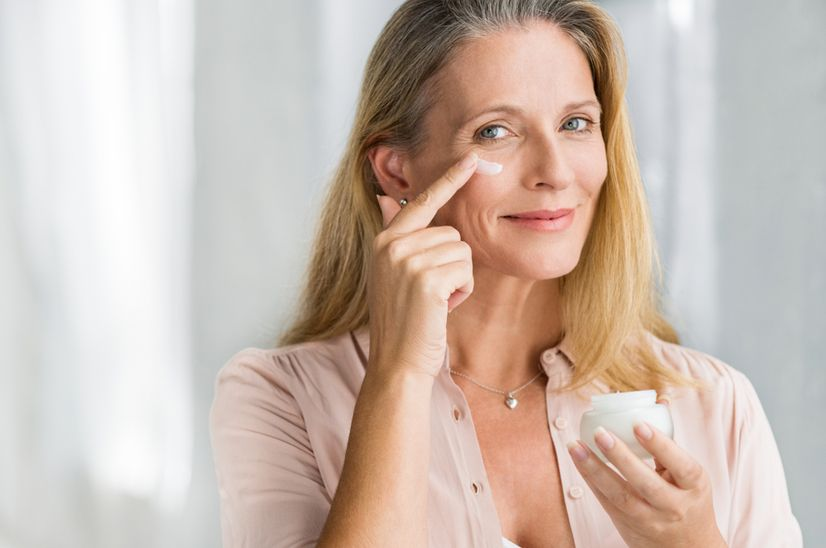 A middle-aged woman applying eye cream to her under-eye area