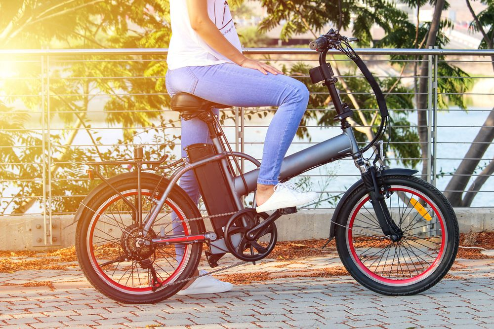 woman sitting on an electric bike with a water view behind her