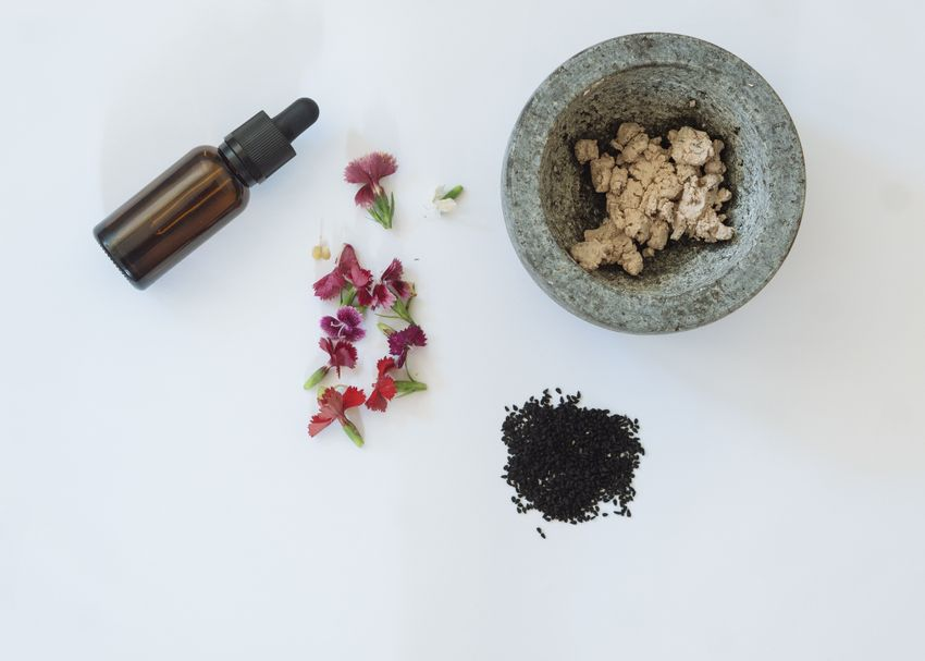 serum, flowers and other natural skincare products arranged neatly