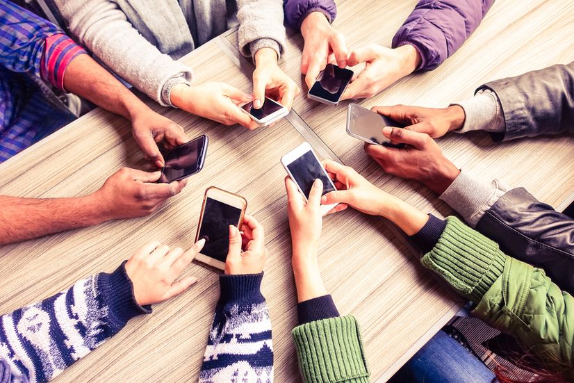 Friends with smartphones in a circle