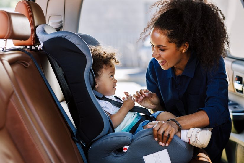 Mother putting baby in car seat restraint