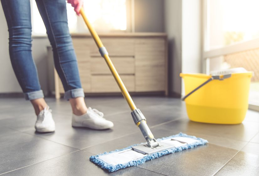 Woman cleaning tiles at home with bucket of liquid floor cleaner