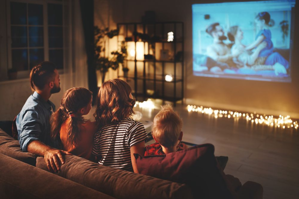 Family watching TV enjoying a projector home set-up