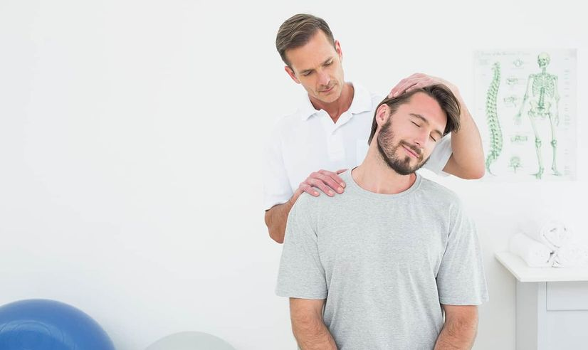 Man looking relaxed as a chiropractor releases tension in his head and neck