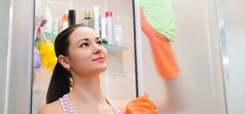 Young woman cleaning glass shower screen