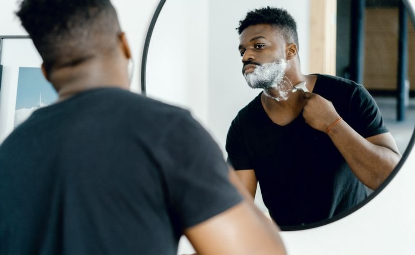 Man shaving his neck in front of the mirror