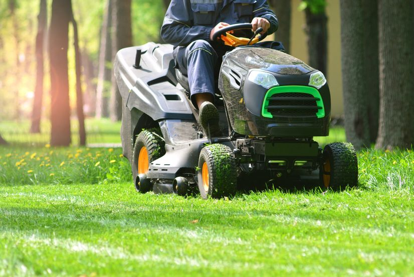A tractor style ride on mower cutting grass in a field