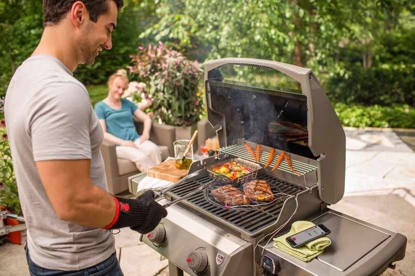 A couple barbequing in garden on a sunny day